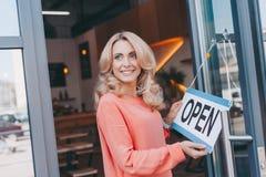 拿着标志的美丽的愉快的咖啡馆所有者开放 免版税库存图片
