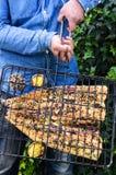 拿着格栅的手包含一条barbequed鱼 库存图片