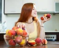 拿着桃子的妇女在家庭厨房里 在果子的焦点 免版税图库摄影