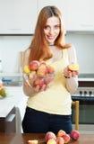 拿着桃子的快乐的妇女在家我 免版税库存照片
