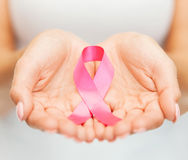 拿着桃红色乳腺癌了悟丝带的手 免版税库存图片