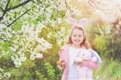 拿着桃红色兔子玩具和鸡蛋的愉快的女孩 免版税图库摄影