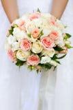 拿着桃红色和白玫瑰的婚礼花束新娘的手 免版税库存照片