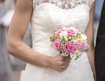 拿着桃红色和白色婚礼花的新娘 免版税库存图片