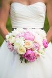 拿着桃红色和白花的婚礼花束新娘 免版税图库摄影