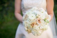 拿着桃红色和白花的婚礼花束新娘 免版税库存照片