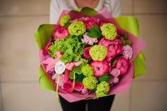 拿着桃红色和绿色花的花束女孩 库存照片