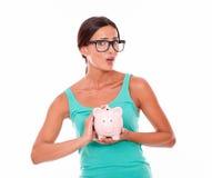 戴拿着桃红色存钱罐的眼镜的震惊妇女 库存照片