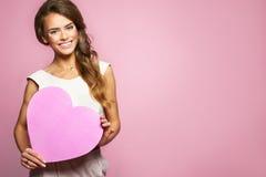 拿着桃红色心脏的愉快的微笑的美丽的妇女 女性式样举行的情人节和爱标志 桃红色背景 免版税库存图片