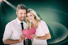 拿着桃红色心脏的有吸引力的年轻夫妇的综合图象 免版税库存照片