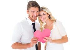 拿着桃红色心脏的有吸引力的年轻夫妇 库存照片