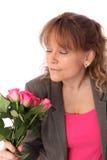 拿着桃红色玫瑰的可爱的妇女 免版税图库摄影
