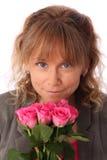 拿着桃红色玫瑰的可爱的妇女 免版税库存图片