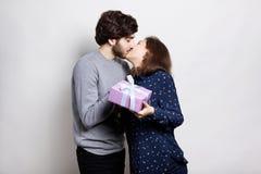 拿着桃红色礼物盒的愉快的夫妇热情地亲吻 爱,关系,约会,恋人,概念射击,在白色bac 库存图片