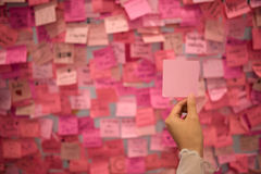 拿着桃红色稠粘的笔记的妇女手 免版税库存照片
