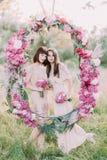拿着桃红色花和身分的花束两个女傧相的可爱的画象在婚礼牡丹后 免版税库存照片