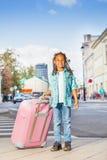 拿着桃红色行李的非洲微笑的女孩在城市 免版税库存照片