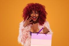 拿着桃红色袋子的购物的美国黑人的妇女被隔绝在橙色背景黑星期五假日 复制空间为 图库摄影