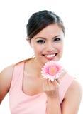拿着桃红色雏菊的逗人喜爱的少妇 库存图片