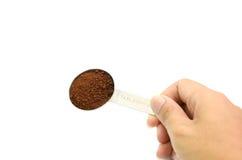 拿着桌匙子用碾碎的咖啡的手 库存图片