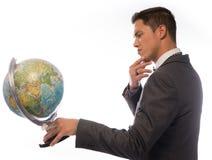 拿着桌面地球的年轻人 免版税库存图片
