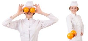 拿着桔子的相当女性医生被隔绝在白色 免版税图库摄影