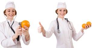 拿着桔子的相当女性医生被隔绝在白色 库存照片