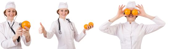 拿着桔子的相当女性医生被隔绝在白色 免版税库存图片