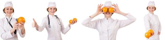 拿着桔子的相当女性医生被隔绝在白色 库存图片