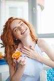 拿着桔子的逗人喜爱的快乐的年轻红头发人夫人 闭合的眼睛 免版税库存照片