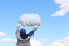 拿着棉绒的云彩回教女孩以夏天天空为背景 免版税库存照片
