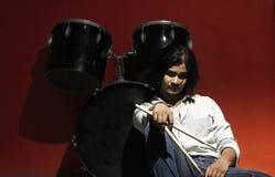 拿着棍子和坐在鼓成套工具旁边的年轻鼓手 图库摄影