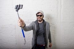 年轻拿着棍子录音selfie的行家时髦博客作者人录影在vlog概念 免版税库存图片