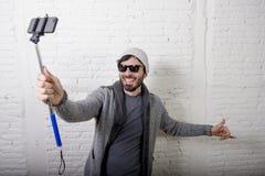 年轻拿着棍子录音selfie的行家时髦博客作者人录影在vlog概念 库存照片