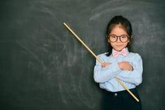 拿着棍子的可爱的矮小的女老师 库存照片