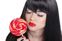 拿着棒棒糖的可爱的深色的女孩 红色嘴唇,长的头发 免版税库存图片