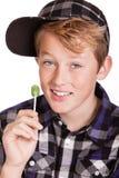 拿着棒棒糖的愉快的时髦年轻男孩 免版税库存照片