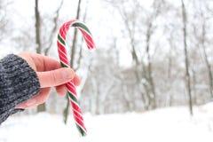 拿着棒棒糖的手 斯诺伊圣诞节风景 背景的被弄脏的照片 免版税库存图片