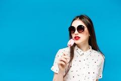 拿着棒棒糖的年轻美丽的妇女被隔绝在蓝色背景 愉快的吃多的女孩佩带的太阳镜色 库存照片