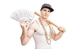 拿着棒球棒和堆金钱的恶棍 图库摄影