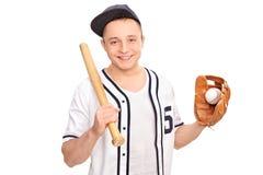 拿着棒球棒和球的年轻人 免版税库存照片