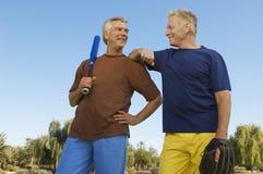 拿着棒球棒和露指手套的男性朋友 免版税库存照片