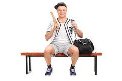 拿着棒球棒的年轻棒球运动员 库存照片