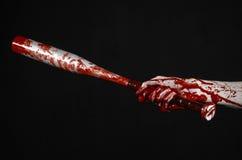 拿着棒球棒,一个血淋淋的棒球棒,棒,流血运动,凶手,蛇神,万圣夜题材,被隔绝的,黑bac的血淋淋的手 库存图片