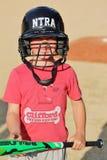 拿着棒的棒球盔甲的逗人喜爱的年轻男孩 免版税库存照片