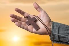 拿着棕色十字架的教士的手在太阳集合 免版税库存照片