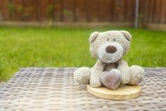 拿着棕色牛奶巧克力心脏的一个逗人喜爱的玩具熊坐圆的木沿海航船上面在塑料藤条的在庭院里 库存照片