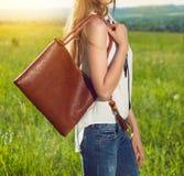 拿着棕色皮革手袋的美丽的女孩户外在晴朗的草甸在日落时间 穿时兴的白色T恤杉的女孩 免版税库存图片