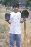 拿着植物和铁锹的一个十几岁的男孩在世界地球日参与时 库存图片