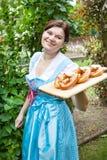 拿着椒盐脆饼的少女装礼服的愉快的美丽的妇女 免版税库存图片